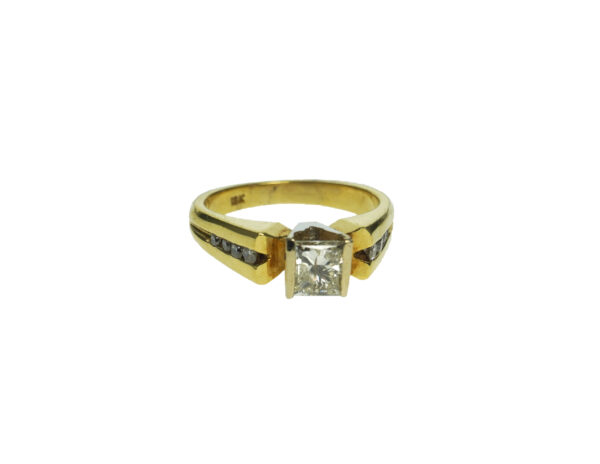yellow gold eighteen karat engagement ring with one princess cut diamond approximately zero point seventy five total carat weight with a total of eight channel set round brilliant diamond chips
