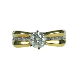 yellow gold bow style eighteen karat engagement style ring with center round brilliant cut diamond one point ten carats and enhanced with a total of eighteen princess cut diamonds approximately zero point zero three carats each