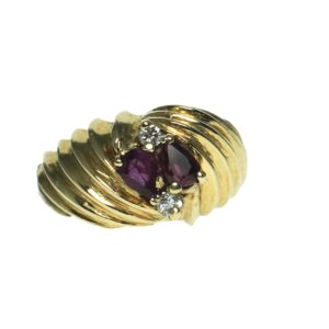 yellow gold fourteen karat raised edge dome style fashion ring with pear shaped rhodolite pear shaped garnet and two round brilliant cut diamonds approximately zero point zero three carats each