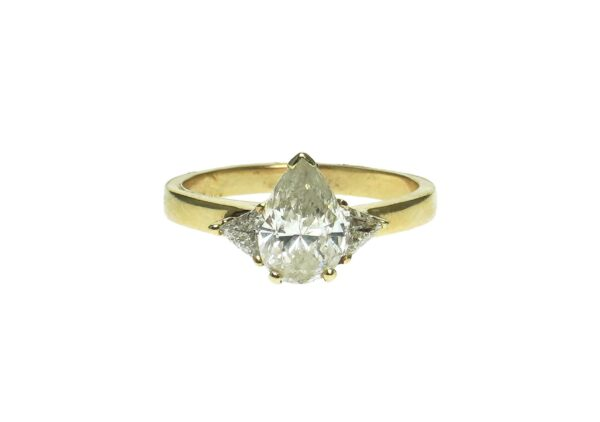 yellow gold fourteen karat engagement ring with center pear shape fractured filled diamond approximately one point zero zero enhanced by one trillion shape diamond approximately zero point zero seven each side