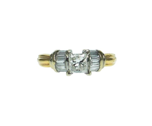 yellow gold fourteen karat two tone setting with princess cut center diamond approximately zero point fifty nine carat accentuated with fourteen baguette diamonds on sides approximately zero point zero four each