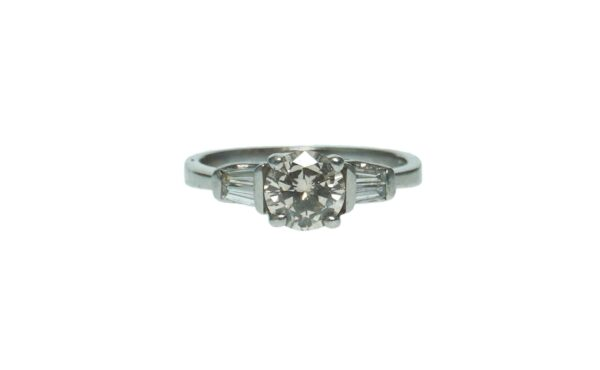 ladies platinum engagement ring with center round brilliant cut diamond approximately one point zero zero carat accentuated with two tapered baguette diamonds on each side