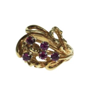 ladies yellow gold fourteen karat ring with five round brilliant red stones set in an open work mounting with tree bark texture